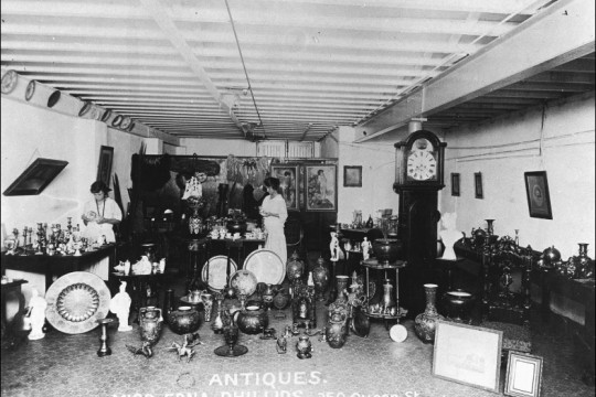 Woman standing in middle of room surrounded by antiques