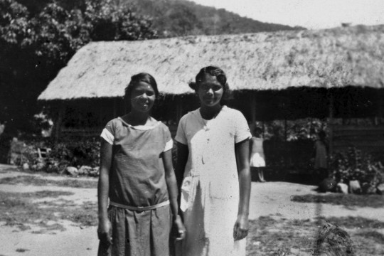 Two Aboriginal girls in front of a grass hut