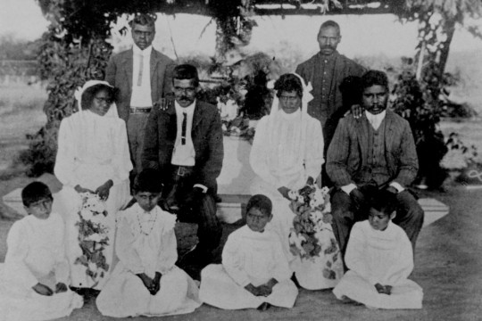 Two Aboriginal brides and their husbands seated with flower children