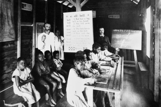 A group of Aboriginal school children in a classroom with two teachers