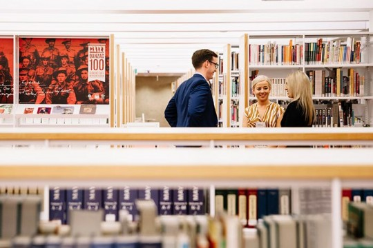 People chatting between the shelves at the State Library