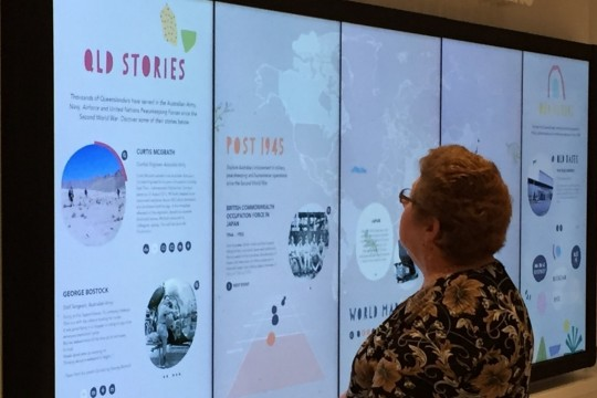 Woman standing in front of Queensland Stories display in Post 1945 Gallery at Anzac Square Memorial Galleries
