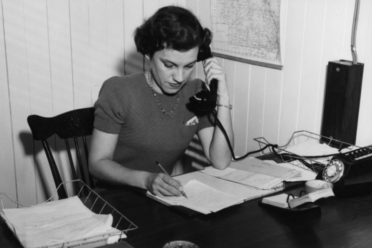 Picture of a woman at a desk talking on the telephone