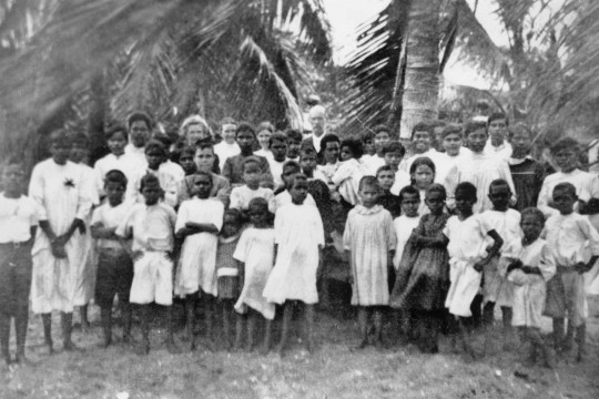 A group of Aboriginal school children standing in front of palm trees
