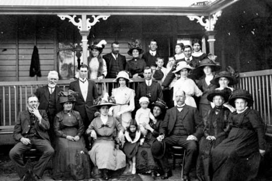 A group of people sitting on the front verandah of a house