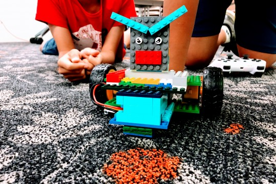 Young people with a custom built Lego robot.