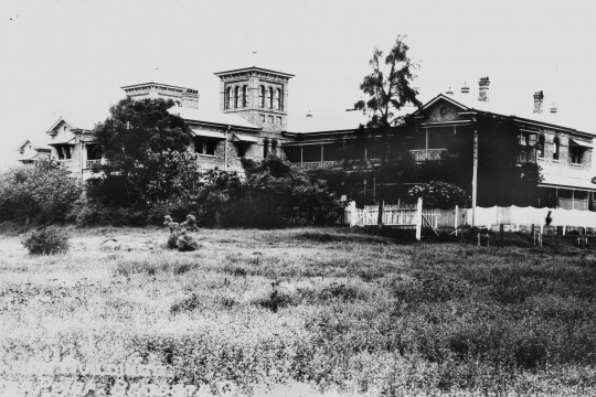 A large brick building on a grassy hill