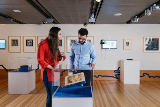 Two people exploring the Islands exhibition