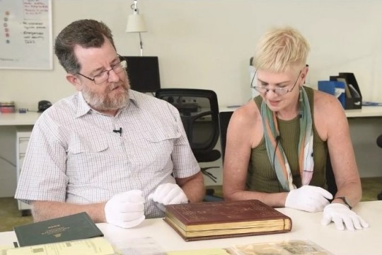 Researchers Matthew Wengert and Louise Martin-Chew explore an item from the collections of the John Oxley Library