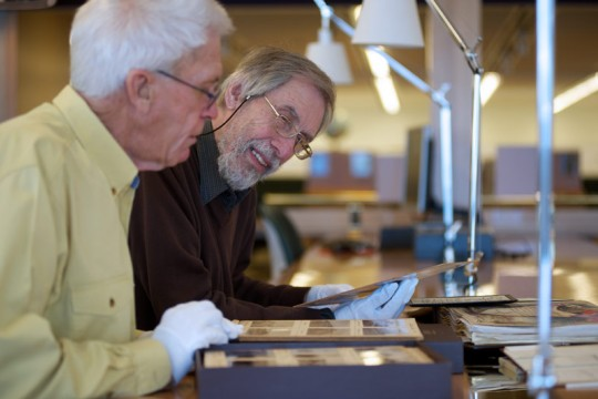 Two men looking at collection items in the State Library