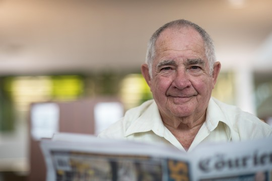 Man reading newspaper in the Caboolture public library.