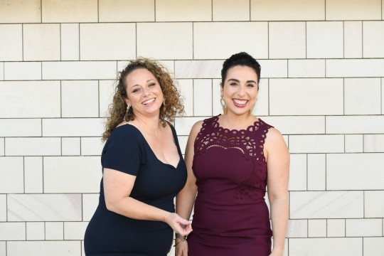 Kristen Souvlis and Nadine Bates from Like A Photon Creative standing together in front of a white brick wall and smiling at the camera
