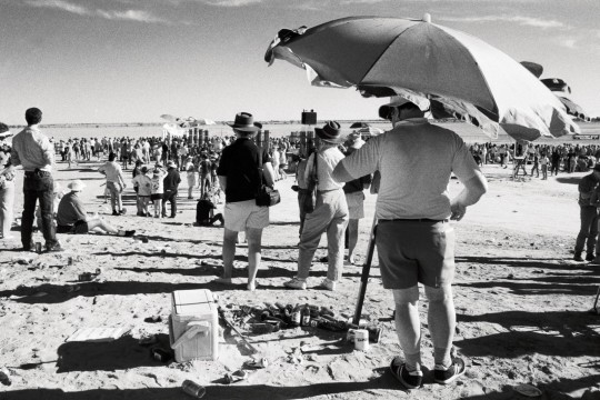 Man with an esky standing under an umbrella at the race track during the Birdsville races Queensland 1990