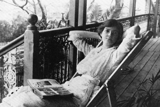 A woman sitting on a verandah with a book open on her lap