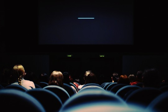 People sitting in seats in front of a screen