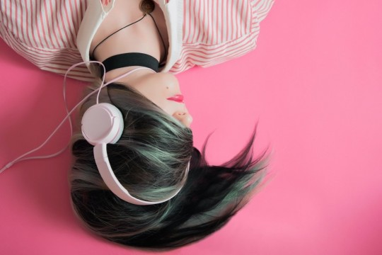 A girl laying down listening to pink headphones