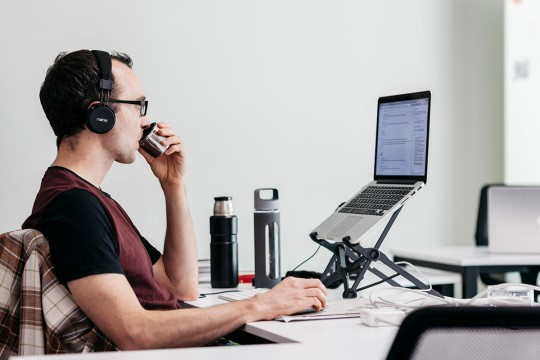 Man sitting at computer with headphones on and drinking coffee