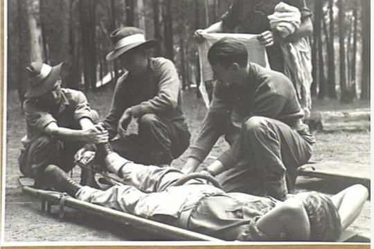 Four soldiers attending to a soldier lying on a stretcher with his right leg in a splint