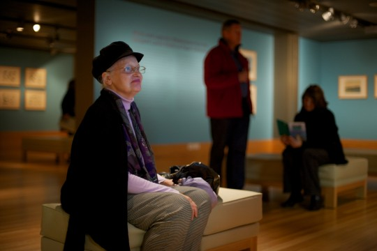 Visitor seated viewing exhibition content