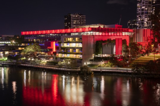 State Library building at night lit red for Remembrance Day
