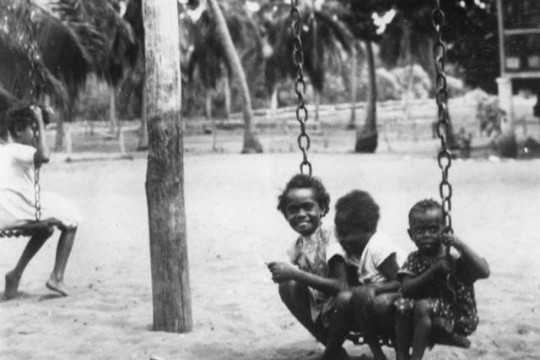 Three children sitting on a swing