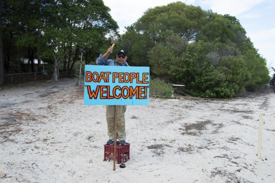 Gordon Hookey placing a sign reading Boat people welcome in the sand in preparation for the arrival of industry representatives by boat Gold Coast Indigenous Artist Camp South Stradbroke Island May 2019