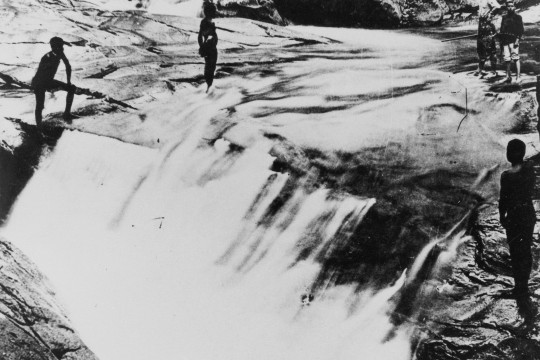Aboriginal people standing above a waterfall near Cairns