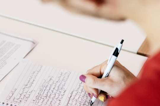Writer making notes in notebook