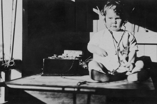 Young child listening to a radio 1920-1930