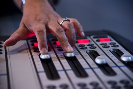 Hand on controls at the 989FM radio station