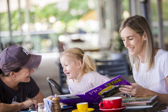 Parents and preschooler sitting at a table at a cafe