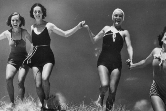 4 women running through grass in swimwear holding hands