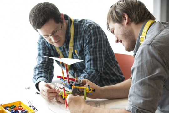 Two men work on a design project with sticks and rubber bands