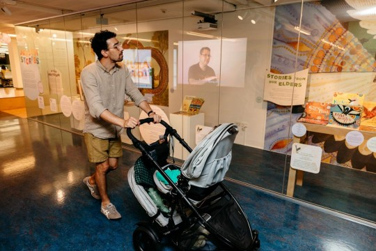 Man will child in stroller exploring the Jarjum Stories showcase at State Library