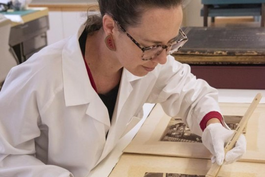 Conservator in white lab coat working on restoring a photo album with a brush