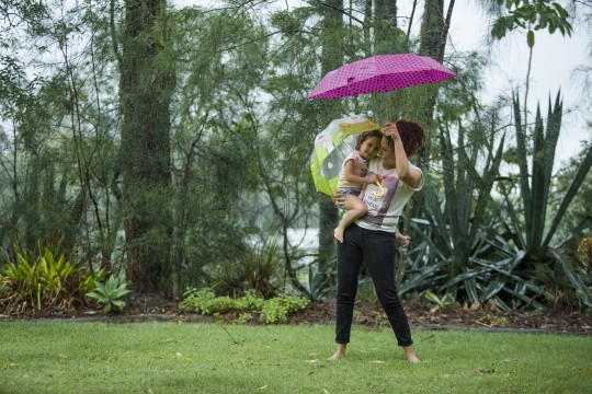 Mother and daughter holding umbrellas and dancing in the rain