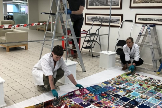Preservation Services staff install the Quarantine Quilt on Level 1 at State Library