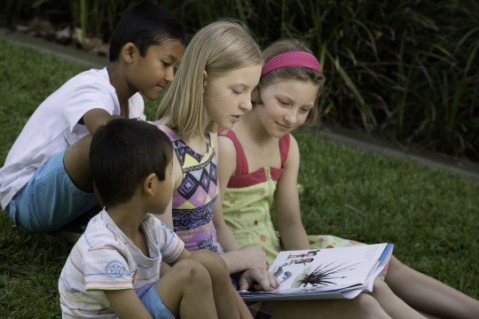 Kids reading on grass 2