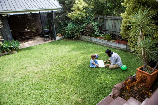 Mother and child reading a book on the grass