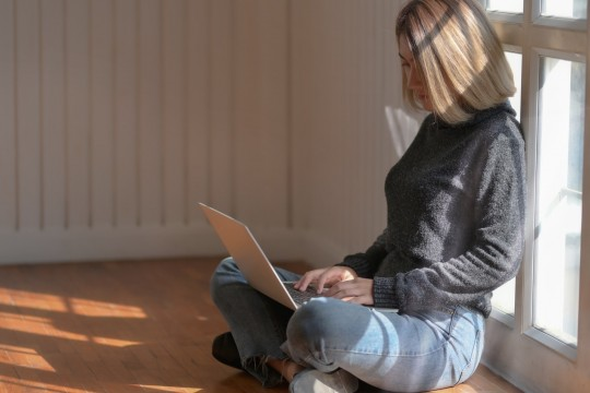 Woman in grey sweater is sitting on the floor and looking at a laptop