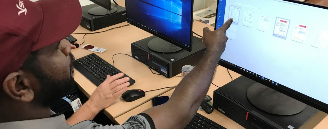 A man points at the computer screen during training