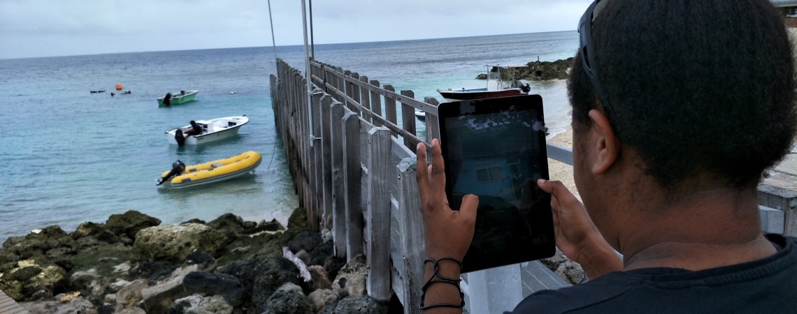A woman uses an iPad to take a picture of a jetty and boats