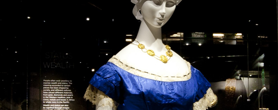 Mannequin in a blue dress wearing the John Watts Necklace as seen in the 2014 exhibition A Fine Possession: Jewellery and Identity. The necklace is an 18 carat gold swag necklace with five openwork carved gold hinged pendants.