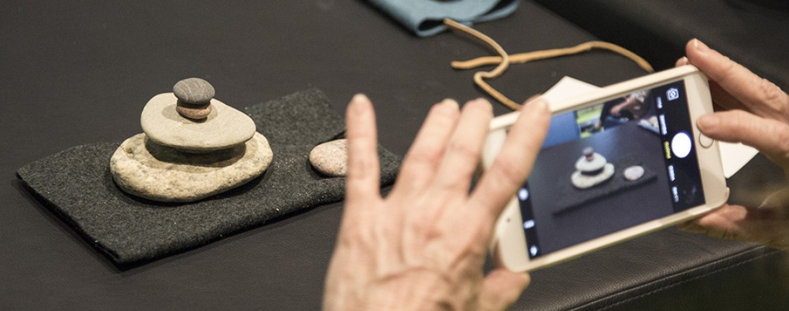 A woman takes an image of a stack of rocks on a table using an iPhone