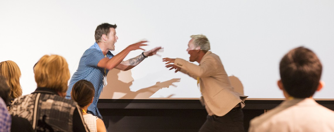Two men raise their arms excitedly during a presentation
