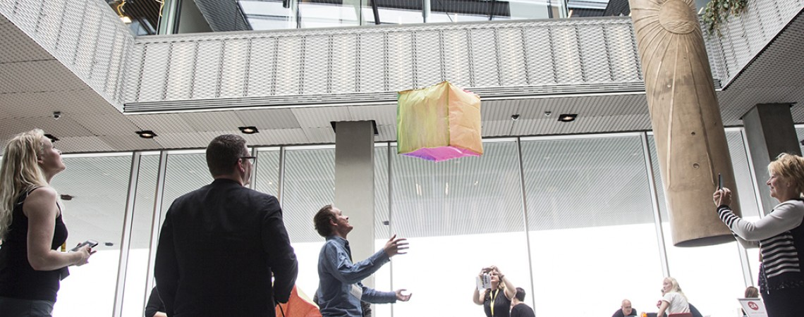 A group of people look on as a square balloon floats above them