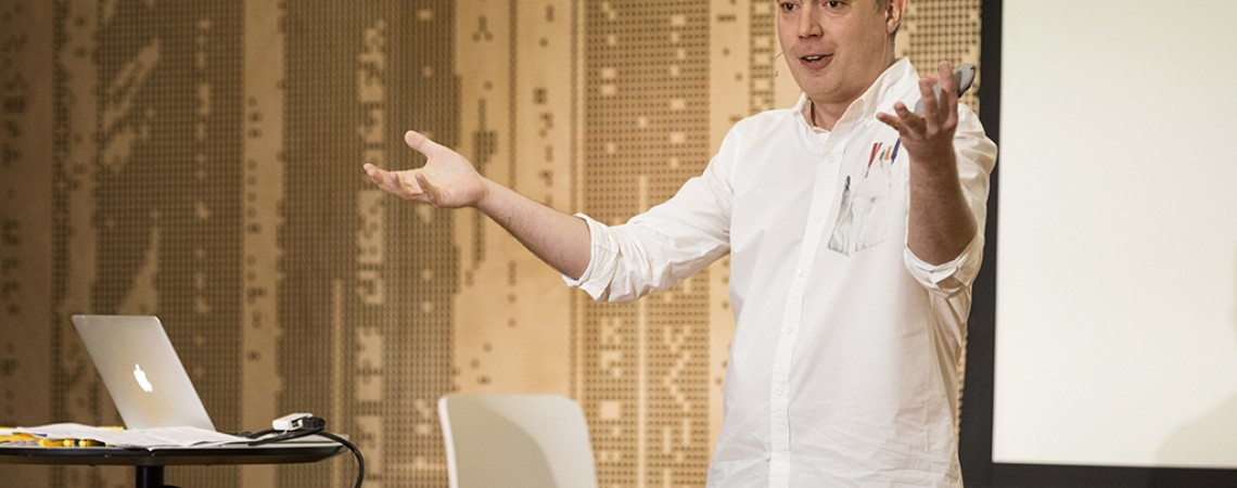 A man delivers a presentation gesturing broadly with his hands