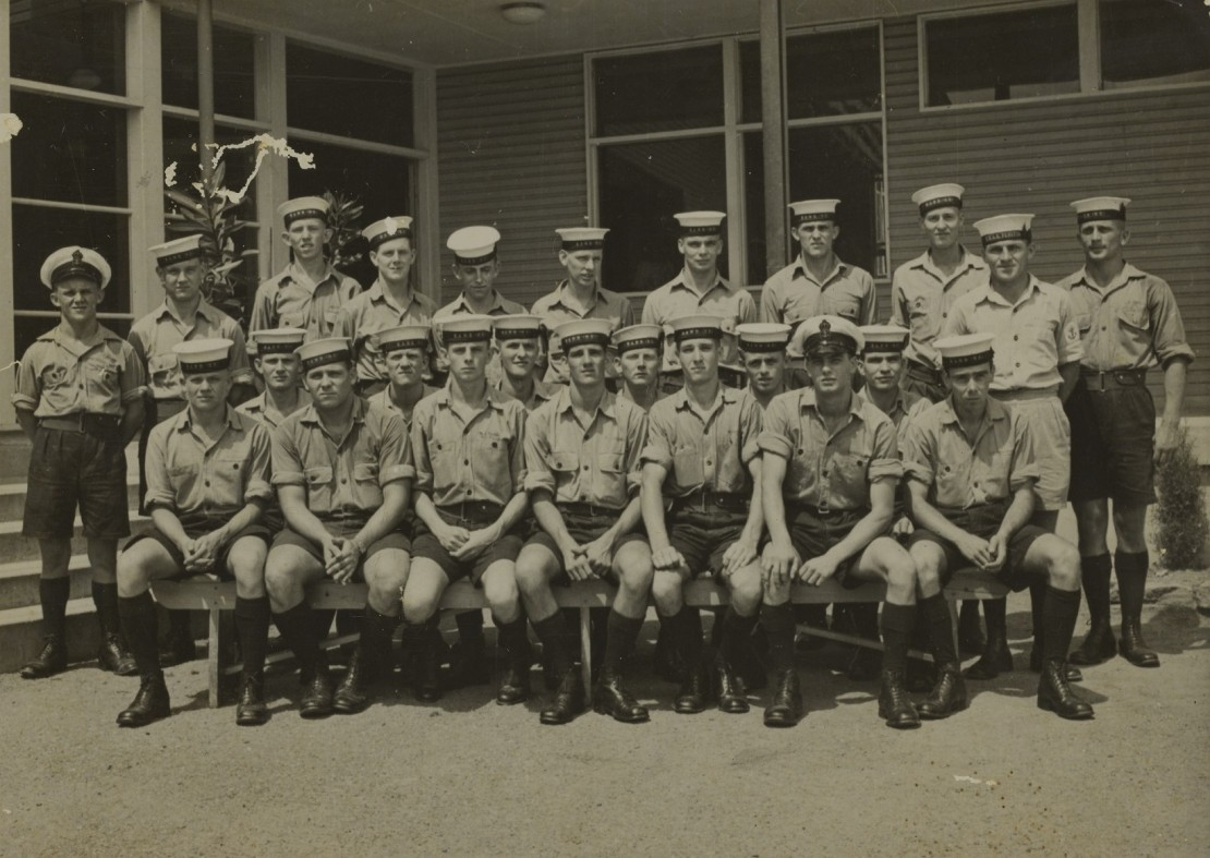 A group of navy recruits in uniform outside a building