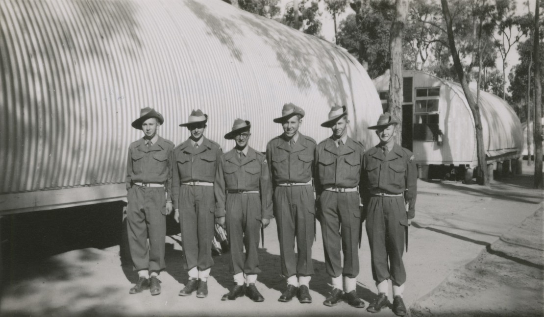 A group of soldiers standing in uniform outside a tin structure