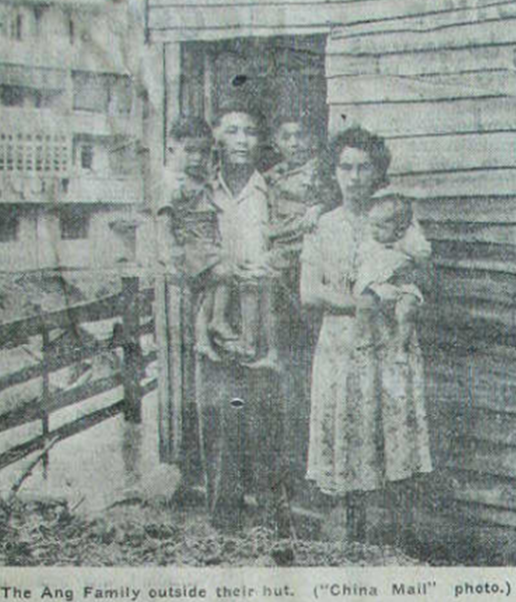 A portrait of a family mother father and three children outside a hut
